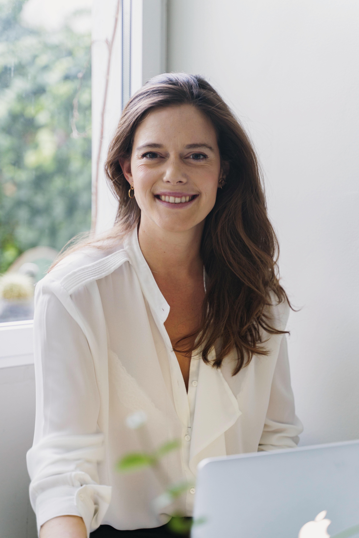 Mujer sonriendo a camara con camisa blanca